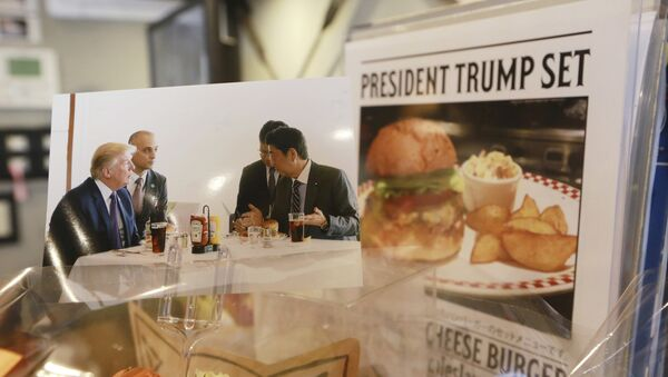 A photo showing U.S. President Donald Trump, left, and Japanese Prime Minister Shinzo Abe, right, at a lunch of hamburgers from Munch's Burger Shack at Kasumigaseki Country Club, is displayed at the burger restaurant in Tokyo Thursday, Nov. 16, 2017 - Sputnik International