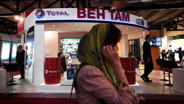 A South Korean businesswoman speaks on her mobile phone in front of the stand of French oil and gas company Total, at Iran's annual International Oil, Gas, Refining & Petrochemical Exhibition in Tehran, on May 6, 2014 - Sputnik International