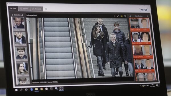 The screen of a computer with an automatic facial recognition system shows German Interior Minister Thomas de Maiziere (2ndR) walking down stairs as he visits the Suedkreuz train station where automatic facial recognition technologies are tested on December 15, 2017 in Berlin - Sputnik International
