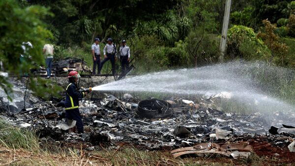 Firefighters work in the wreckage of a Boeing 737 plane that crashed in the agricultural area of Boyeros, around 20 km (12 miles) south of Havana, shortly after taking off from Havana's main airport in Cuba, May 18, 2018. - Sputnik International