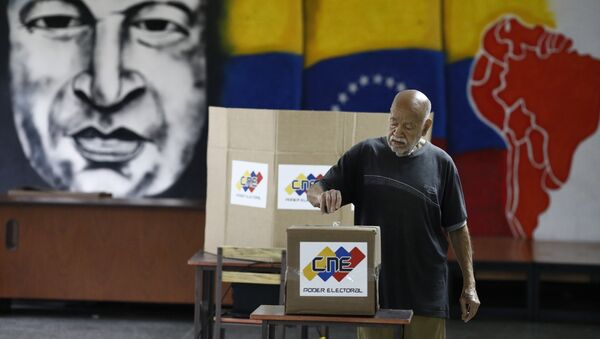 With an image of the late Venezuelan President Hugo Chavez behind him a Venezuelan citizen casts his vote at a polling station during the presidential election in Caracas, Venezuela, May 20, 2018 - Sputnik International