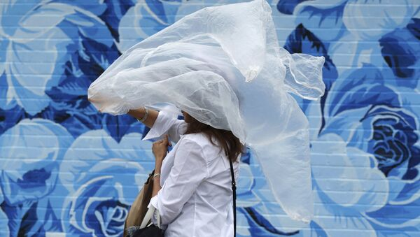 A woman puts on a plastic cover before the 144th running of the Kentucky Derby horse race - Sputnik International