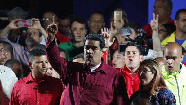 Venezuela's President Nicolas Maduro raises a finger as he is surrounded by supporters while speaking during a gathering after the results of the election were released, outside of the Miraflores Palace in Caracas, Venezuela, May 20, 2018 - Sputnik International