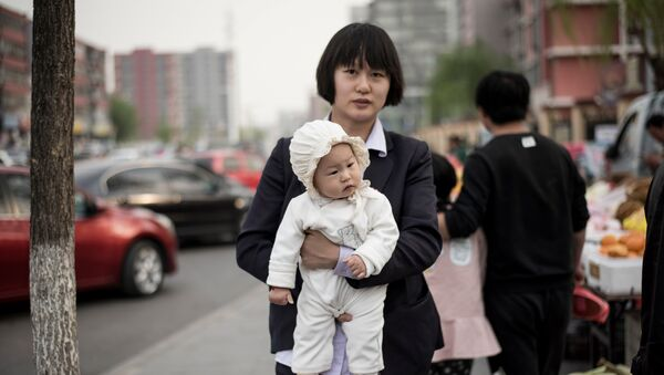 A mother holds her baby as she walks in a market in Shunyi on the outskirts of Beijing on April 13, 2017 - Sputnik International