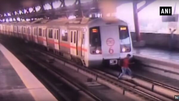 Watch video: Man crosses tracks at Delhi Metro station as train starts moving - Sputnik International