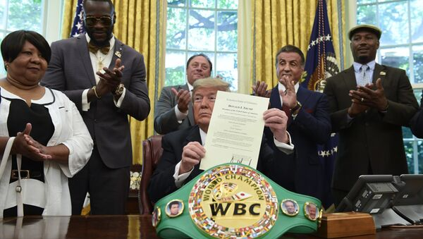 President Trump holds up the pardon as Deontay Wilder (left) and Lennox Lewis (right) applaud - Sputnik International