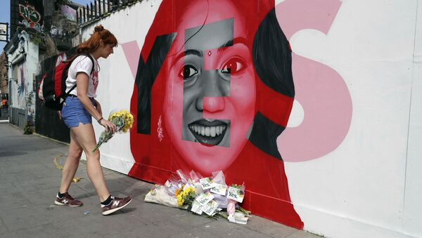 A woman places flowers by a mural showing Savita Halappanavar, a 31-year-old Indian dentist who had sought and been denied an abortion before she died after a miscarriage in a Galway hospital, with the word YES over it, in Dublin, Ireland, on the day of a referendum on the 8th amendment of the constitution. - Sputnik International