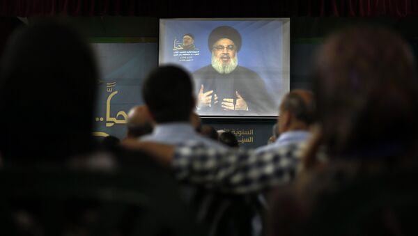 Hezbollah leader Sheik Hassan Nasrallah speaks on a screen via a video link during a ceremony to mark the second anniversary of the death of Hezbollah top commander, Mustafa Badreddine, who was killed in an explosion in Damascus, in the southern suburbs of Beirut, Lebanon, Monday, May 14, 2018 - Sputnik International