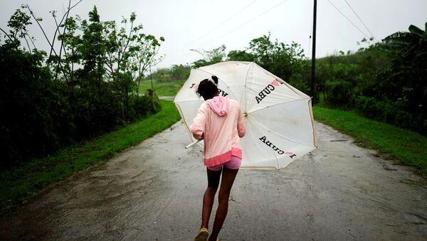 Dalma Samora, 14, walks against the winds of Subtropical Storm Alberto as it passes by the west coast of Cuba, in La Palma, Cuba, May 26, 2018. - Sputnik International