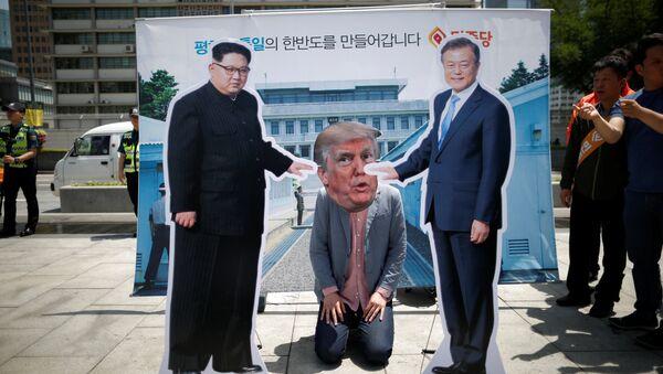 A man wearing a mask of U.S. President Donald Trump kneels down between cutouts of North Korean leader Kim Jong Un and South Korean President Moon Jae-in during an anti-U.S. President Donald Trump rally near U.S. embassy in Seoul, South Korea, May 25, 2018 - Sputnik International