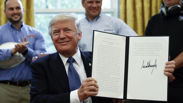 President Donald Trump holds up a National Manufacturing Day Proclamation after signing it in the Oval Office of the White House in Washington, Friday, Oct. 6, 2017 - Sputnik International