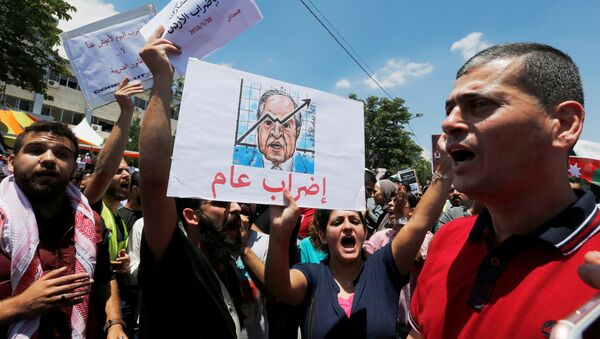A Jordanian protester holds a picture of Jordanian Prime Ministers Hani al-Mulki and chants slogans during a strike against the new income tax law, in Amman, Jordan May 30, 2018 - Sputnik International