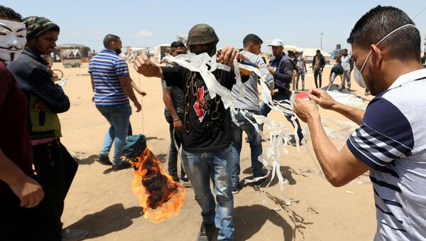 Palestinian demonstrators prepare to set a kite on fire to be thrown at the Israeli side during a protest demanding the right to return to their homeland, at the Israel-Gaza border in the southern Gaza Strip, May 11, 2018 - Sputnik International