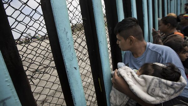 In this April 29, 2018 file photo, a member of the Central American migrant caravan, holding a child, looks through the border wall toward a group of people gathered on the U.S. side, as he stands on the beach where the border wall ends in the ocean, in Tijuana, Mexico, Sunday, April 29, 2018 - Sputnik International