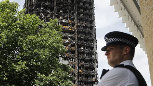 A police officer stands near to the burnt Grenfell Tower apartment building standing testament to the recent fire in London, Friday, June 23, 2017.  - Sputnik International