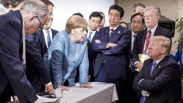 German Chancellor Angela Merkel, center, details policy to US President Donald Trump, seated at right, during the G7 Leaders Summit in La Malbaie, Quebec, Canada, on Saturday, June 9, 2018 - Sputnik International