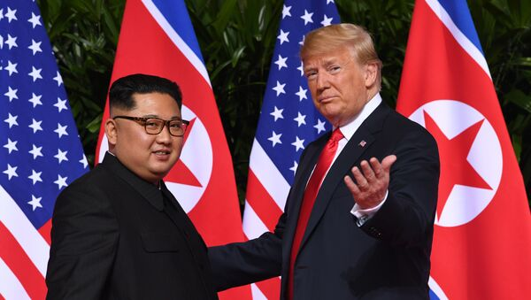 US President Donald Trump (R) gestures as he meets with North Korea's leader Kim Jong Un (L) at the start of their historic US-North Korea summit, at the Capella Hotel on Sentosa island in Singapore on June 12, 2018. - Sputnik International