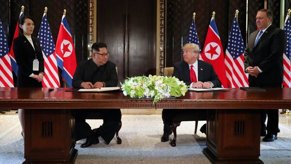U.S. President Donald Trump and North Korea's leader Kim Jong Un look at each others before signing documents that acknowledge the progress of the talks and pledge to keep momentum going, after their summit at the Capella Hotel on Sentosa island in Singapore June 12, 2018 - Sputnik International