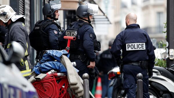French police and a fireman secure the street as a man has taken people hostage at a business in Paris, France, June 12, 2018 - Sputnik International