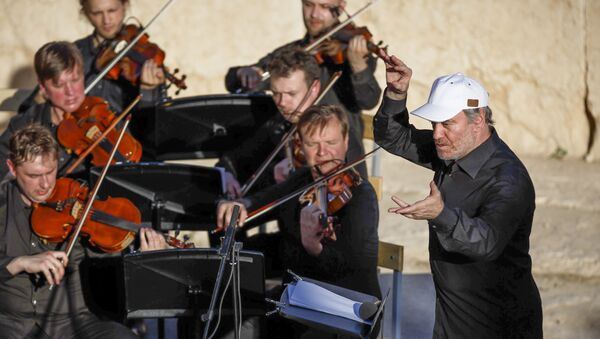 In this Thursday, May 5, 2016 photo provided by Russian Defense Ministry Press Service, the renowned conductor Valery Gergiev, right, leads a performance by the Mariinsky Symphony Orchestra from St. Petersburg, during the concert at the UNESCO world heritage site of Palmyra, the central city of Homs, Syria - Sputnik International