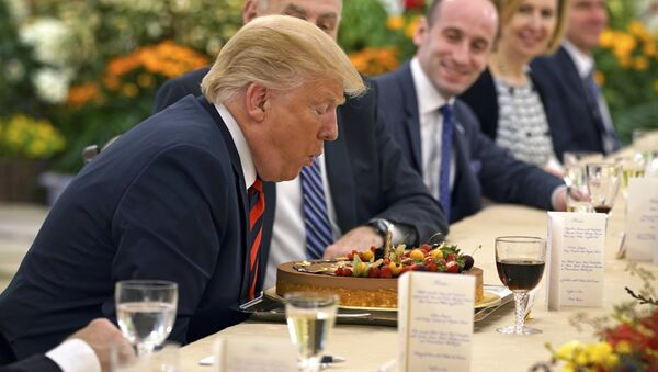 In this photo released by the Ministry of Communications and Information of Singapore, U.S. President Donald Trump blows out a candle on a cake celebrating an early birthday during lunch with Singapore's Prime Minister Lee Hsien Loong in Singapore, Monday, June 11, 2018 - Sputnik International