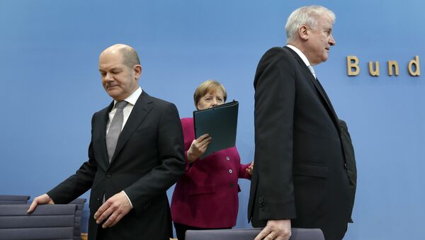 In this March 12, 2018 photo, from left, Olaf Scholz, acting chairman of the German Social Democratic Party (SPD), German Chancellor and chairwoman of the German Christian Democratic Union (CDU), Angela Merkel, and the chairman of the German Christian Social Union (CSU), Horst Seehofer, arrive for a joint press conference in Berlin, Germany - Sputnik International