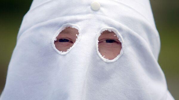 An unidentified member of the Ku Klux Klan peers from beneath a hooded mask at a Ku Klux Klan rally Saturday, June 10, 2006 - Sputnik International