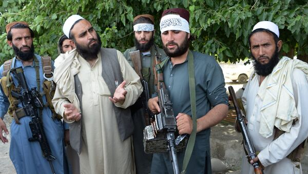 Afghan Taliban militants stand with residents as they took to the street to celebrate ceasefire on the second day of Eid in the outskirts of Jalalabad on June 16,2018 - Sputnik International