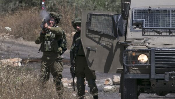 Israeli soldiers take position as Palestinian protesters clash with Israeli forces during a weekly demonstration against the expropriation of Palestinian land by Israel in the village of Kfar Qaddum, near Nablus in the occupied West Bank on May 18, 2018 - Sputnik International