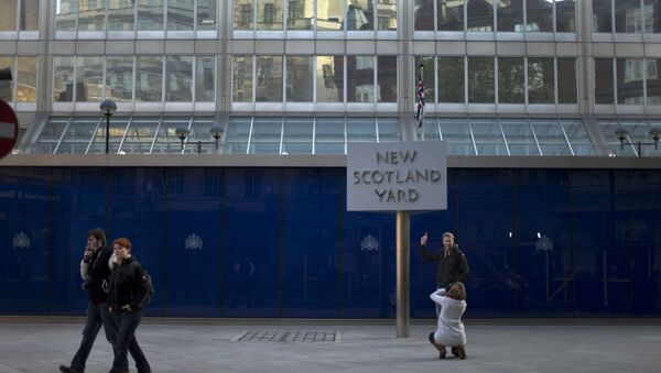 A tourist poses for a photograph by the rotating sign outside New Scotland Yard, the headquarters building of London's Metropolitan Police force in central London - Sputnik International