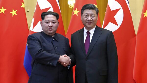 In this photo provided Wednesday, March 28, 2018, by China's Xinhua News Agency, North Korean leader Kim Jong Un, left, and Chinese President Xi Jinping shake hands in Beijing, China. - Sputnik International
