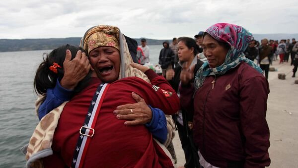Relatives cry while waiting for news on missing family members who were on a ferry that sank yesterday in Lake Toba, at Tigaras Port, Simalungun, North Sumatra, Indonesia June 19, 2018 - Sputnik International