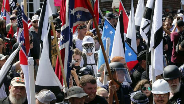 In this Saturday, Aug. 12, 2017, file photo, white nationalist demonstrators walk into the entrance of Lee Park surrounded by counter demonstrators in Charlottesville, Va. - Sputnik International