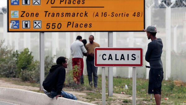 Migrants stand near a city sign along a road near the makeshift camp called The New Jungle in Calais, France, August 19, 2015 - Sputnik International