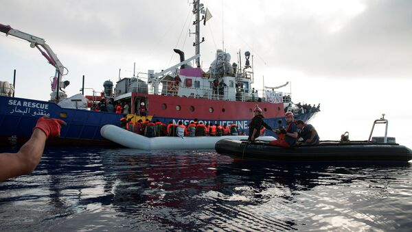 Migrants are seen in a rubber dinghy as they are rescued by the crew of the Mission Lifeline rescue boat in the central Mediterranean Sea, June 21, 2018 - Sputnik International