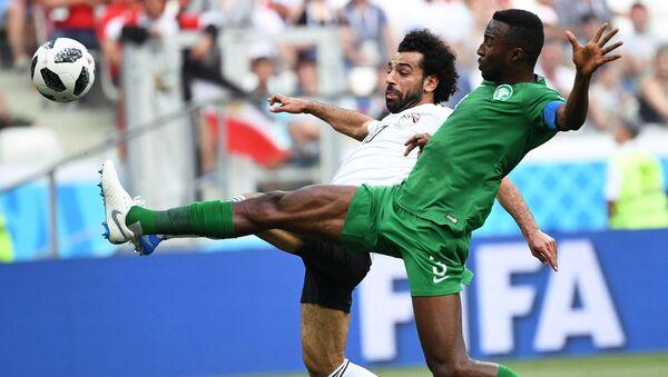 Soccer Football - World Cup - Group A - Saudi Arabia vs Egypt - Volgograd Arena, Volgograd, Russia - June 25, 2018 Egypt's Mohamed Salah in action with Saudi Arabia's Osama Hawsawi - Sputnik International