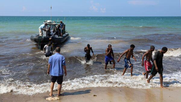 Migrants leave a boat at the coast of Tajoura, east of Tripoli, Libya June 20, 2018 - Sputnik International