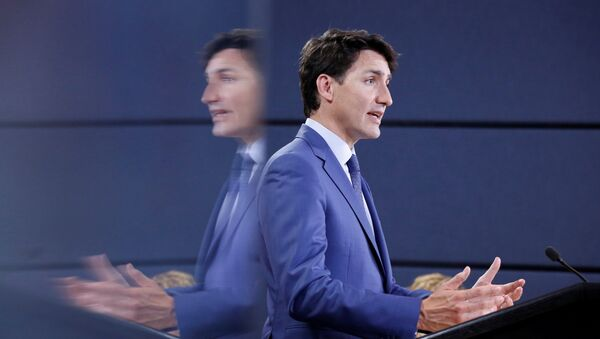 Canada's Prime Minister Justin Trudeau is reflected in a monitor while speaking during a news conference in Ottawa, Ontario, Canada, June 20, 2018 - Sputnik International