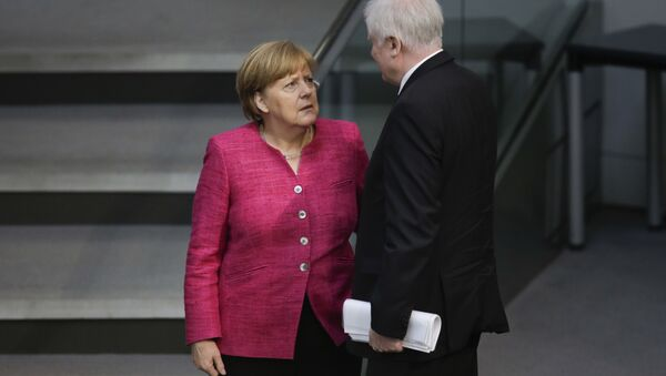 In this May 15, 2018 file photo German Chancellor Angela Merkel, left, talks with German Interior Minister Horst Seehofer, right, during the first day of the budget 2018 debate at the parliament Bundestag at the Reichstag building in Berlin - Sputnik International