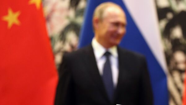 The Russian and Chinese national flags are seen on the table as Russia's President Vladimir Putin (back L) and his China's President Xi Jinping (back R) stand during a signing ceremony at the Diaoyutai State Guesthouse in Beijing on November 9, 2014. - Sputnik International