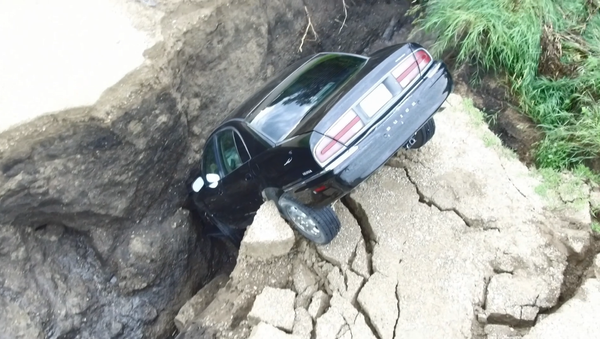 Screenshot From Drone Footage of a Minnesota Driver's Car that Plunged into a Hole Created by Rain, July 3, 2018 - Sputnik International