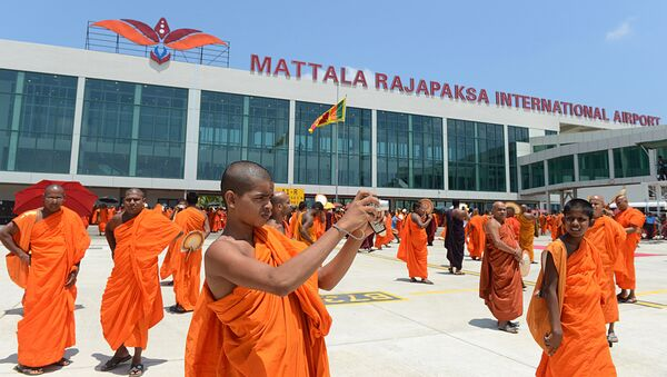(File) A Sri Lankan Budhist monk takes pictures of an unseen Sri Lankan airlines Airbus A-340 which transported President Mahinda Rajapakse who became the first passenger to go through the facility, at the new Mattala Rajapaksa International Airport in Mattala, in the southeast of the island on March 18, 2013 - Sputnik International