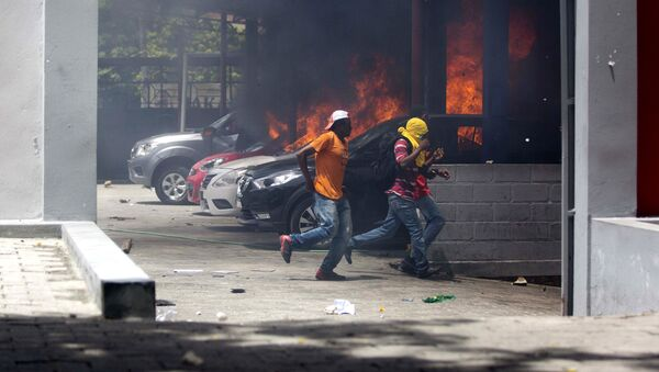 People run away after cars were set on fire at a Nissan dealership during protests over a fuel price increase in Port-au-Prince, Haiti, on Saturday, July 7, 2018 - Sputnik International