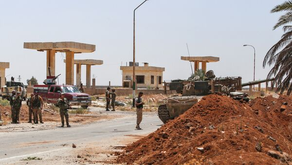 Syrian government soldiers stand by a tank and armed pickup trucks at the Nassib border crossing with Jordan in the southern province of Daraa on July 7, 2018 - Sputnik International