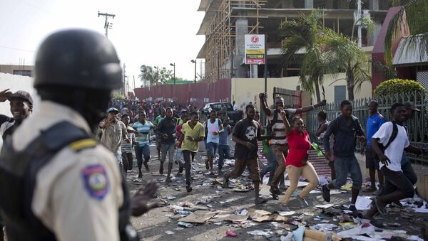 A police officer looks on as a crowd enters the Delimart supermarket complex, which had been burned during two days of protests against a planned hike in fuel prices in Port-au-Prince, Haiti, Sunday, July 8, 2018. - Sputnik International