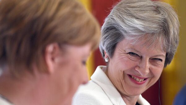Britain's Prime Minister Theresa May, and Germany's Chancellor Angela Merkel hold a news conference with Polish Prime Minister, Mateusz Morawiecki (unseen) during the Western Balkans Summit 2018 at Lancaster House in London, Britain, July 10, 2018 - Sputnik International