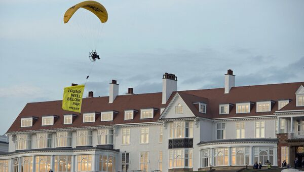 In this Friday, July 13, 2018 photo, a Greenpeace protester flying a microlight passes over US President's Donald Trump's resort in Turnberry, South Ayrshire, Scotland with a banner reading Trump: Well Below Par, shortly after the US President arrived at the hotel. Scottish police said the protester breached a no-fly zone over Turnberry hotel and committed a criminal offence. - Sputnik International