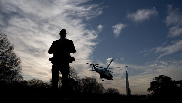 A Secret Service agent stands guard as Marine One with President Donald Trump aboard departs the White House in Washington, Saturday, Dec. 2, 2017, for a short trip to Andrews Air Force Base, Md. where Trump will travel to New York for a fundraising event - Sputnik International
