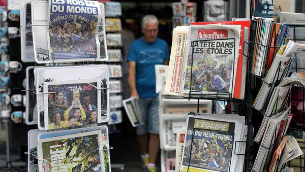 A man walks past racks which display copies of French daily newspapers with front pages about France's win in the World Cup, in Nice, France, July 16, 2018 - Sputnik International