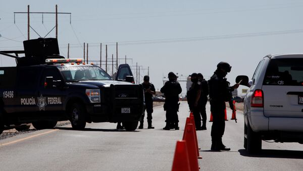 A federal police officer (R) inspect a vehicle at a security checkpoint near a prison in Ciudad Juarez where Mexican drug boss Joaquin Chapo Guzman has been moved from his jail in central Mexico May 7, 2016 - Sputnik International